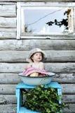 Kleines schönes Baby in der Abwaschschüssel vor dem hintergrund einer Wand des Holzhauses Stockbild