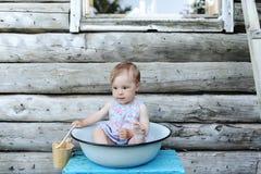 Kleines schönes Baby in der Abwaschschüssel vor dem hintergrund einer Wand des Holzhauses Lizenzfreie Stockfotos