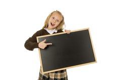 Kleines schönes blondes lächelndes Schulmädchen glückliche und nette kleine leere Tafel der Holding und der Vertretung Lizenzfreie Stockfotografie