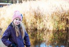 Kleines schönes blondes Mädchen im rosa Hut auf Hintergrund von herbstlichem See Stockfotos