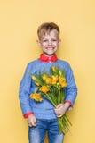 Kleines schönes Kind mit einem Blumenstrauß von Tulpen Sohn gibt Mutterblumen an Frauen ` s Tag, Mutter ` s Tag Geburtstag Valent Lizenzfreie Stockbilder