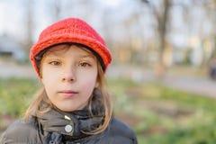 Kleines schönes lächelndes Mädchen im roten Hut Stockfoto