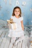 Kleines schönes lächelndes Mädchen mit einem Geschenk in ihren Händen Lizenzfreies Stockbild