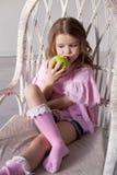 Kleines schönes Mädchen, das apfelgrüne Zähne isst lizenzfreie stockfotos