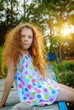 Kleines schönes Mädchen, das auf Brücke sitzt Lizenzfreies Stockfoto