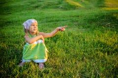 Kleines schönes Mädchen, das auf Gras sitzt Stockbilder