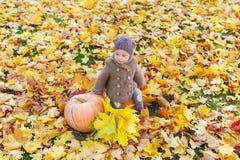 Kleines schönes Mädchen in der warmen Kleidung sitzt mit Kürbis unter Herbstlaub Lizenzfreie Stockfotografie