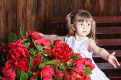 Kleines schönes Mädchen im weißen Kleid umarmt großen Blumenstrauß Stockfotografie