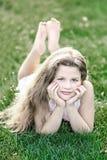 Kleines schönes Mädchen mit dem langen losen Haar auf grünem Gras am Sommertag Stockfotos