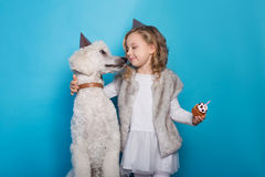 Kleines schönes Mädchen mit Hund feiern Geburtstag Freundschaft Liebe Kuchen mit Kerze Studioporträt über blauem Hintergrund Lizenzfreies Stockfoto