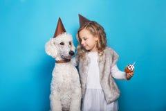 Kleines schönes Mädchen mit Hund feiern Geburtstag Freundschaft Liebe Kuchen mit Kerze Studioporträt über blauem Hintergrund Stockfotografie