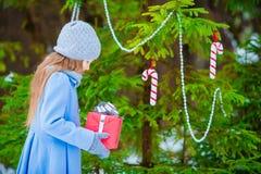Kleines schönes Mädchen mit Weihnachtskastengeschenk am Wintertag draußen Neues Jahr bald kommend Stockfotografie