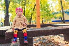 Kleines schönes Mädchen sitzt auf einer Bank im Herbst Lizenzfreie Stockfotos
