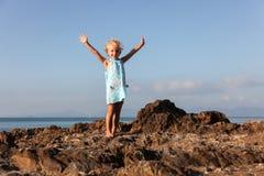 Kleines schönes Mädchen steht auf der felsigen Küste von den angehobenen Händen Stockfotografie
