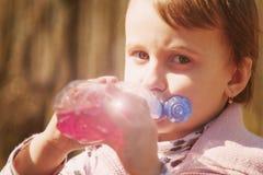 Kleines schönes Mädchenkind, das den geschmackvollen natürlichen Saft im Freien trinkt lizenzfreies stockbild