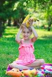 Kleines schönes Mädchenkinderkind, das auf Gras mit Bananen sitzt Stockfotos