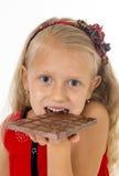 Kleines schönes weibliches Kind im roten Kleid, das glücklichen köstlichen Schokoriegel in ihrem Handessen erfreut hält Stockbilder