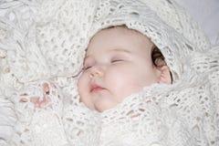 Kleines schlafendes Baby liegt in gestrickten Schalen Lizenzfreie Stockfotografie