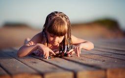 Kleines schönes Mädchen, das auf der Brücke spielt Stockfotos