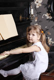 Kleines schönes Mädchen im weißen Kleid sitzt am Klavier Stockbild