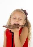 Kleines schönes weibliches Kind im roten Kleid, das glücklichen köstlichen Schokoriegel in ihrem Handessen erfreut hält Lizenzfreies Stockbild