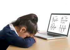 Kleines Schulmädchen gebohrt und mit Computermathehausarbeit ermüdet Stockfoto