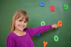 Kleines Schulmädchen, das auf einen Buchstaben zeigt Lizenzfreie Stockfotos