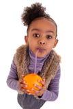 Kleines schwarzes Mädchen, das Orangensaft trinkt lizenzfreies stockfoto