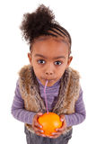 Kleines schwarzes Mädchen, das Orangensaft trinkt lizenzfreie stockbilder