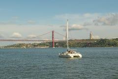 Kleines Segelboot, das in Richtung zur Brücke am 25. April in Lissabon sich bewegt Lizenzfreie Stockfotos
