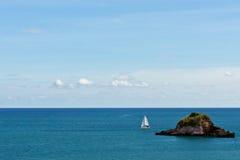 Kleines Segelnboot und eine Insel Stockfoto