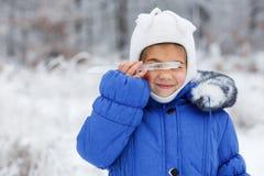 Kleines sehr nettes Mädchen im Winter auf dem Hintergrund des schneebedeckten Sonnenuntergangwaldes, Abschluss oben Lizenzfreie Stockbilder