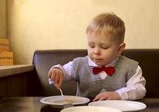 Kleines Sitzen des kleinen Jungen Stockfoto