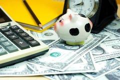 Kleines Sparschwein und Finanztaschenrechner auf Stapel von US-Dollar Lizenzfreies Stockfoto