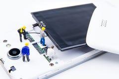 Kleines Spielwarenminiaturteam von Ingenieuren tun Änderungsbatterien Lizenzfreie Stockfotografie