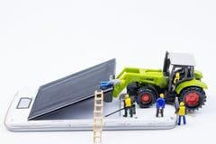 Kleines Spielwarenminiaturteam von Ingenieuren tun Änderungsbatterien Stockfotos