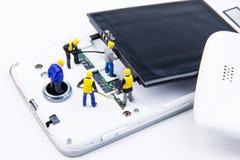 Kleines Spielwarenminiaturteam von Ingenieuren tun Änderungsbatterien Stockbild
