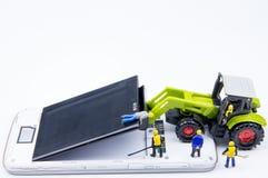 Kleines Spielwarenminiaturteam von Ingenieuren tun Änderungsbatterien Stockfoto