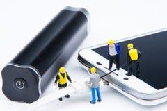 Kleines Spielwarenminiaturteam von Ingenieuren tun verbundenes Kabel Lizenzfreie Stockfotografie