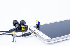 Kleines Spielwarenminiaturteam von Ingenieuren tun verbundenes Kabel Stockfotografie