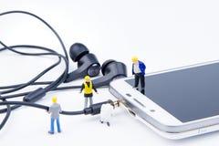 Kleines Spielwarenminiaturteam von Ingenieuren tun verbundenes Kabel Stockbild