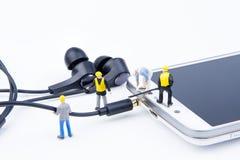 Kleines Spielwarenminiaturteam von Ingenieuren tun verbundenes Kabel Stockfotos