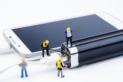 Kleines Spielwarenminiaturteam von Ingenieuren tun verbundenes Kabel Lizenzfreies Stockfoto