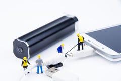 Kleines Spielwarenminiaturteam von Ingenieuren tun verbundenes Kabel Lizenzfreie Stockbilder