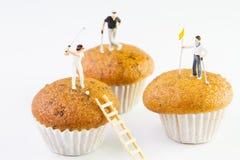 Kleines Spielzeug, das Golf auf kleinen Kuchen spielt Lizenzfreies Stockfoto