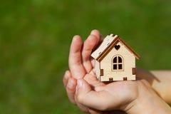 Kleines Spielzeughaus in den Händen des Kindes auf Hintergrund des grünen Grases Konzepthypothek, Traumhaus, Immobilienerwerb lizenzfreie stockfotos