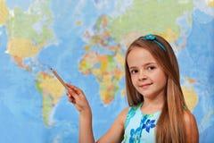 Kleines Studentenmädchen, das auf undeutliche Weltkarte zeigt Stockbild