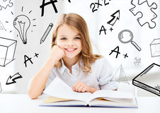 Kleines Studentenmädchen, das in der Schule studiert Stockfotografie