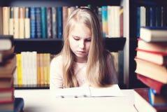 Kleines Studentenmädchenin der schule studieren und -lesebuch Stockfotografie