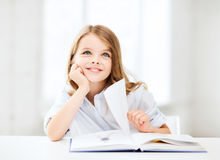 Kleines Studentenmädchen, das in der Schule studiert Lizenzfreies Stockbild